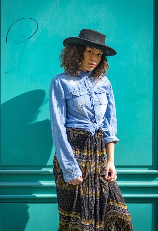 Chapeau noir Femme, chemise Levis et longue jupe. Friperie